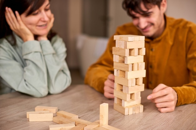 Couple playing to build a tower of wooden blocks at home hanging out with friends