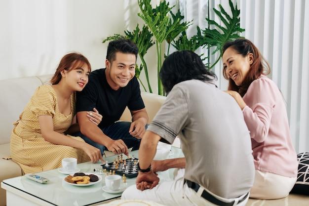 Пара играет в шахматы с родителями