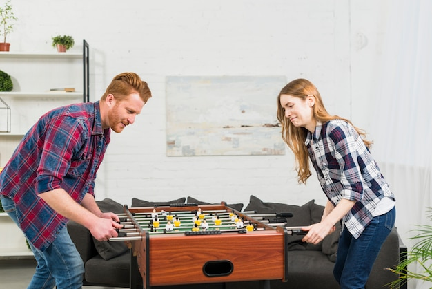 Couple playing football table soccer game at home