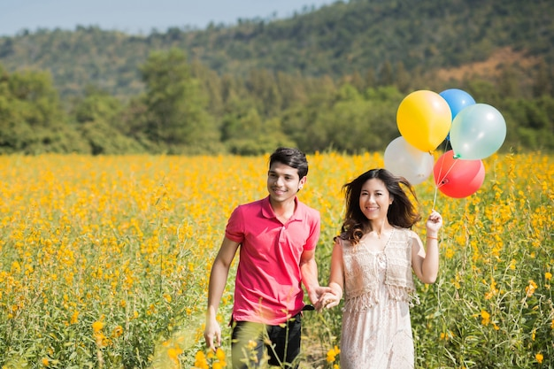 Couple playing in the garden flowers yellow balloons.