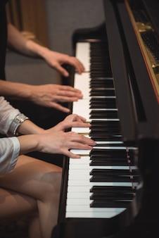 Couple playing a piano