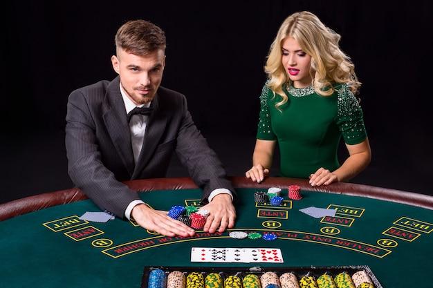 緑のテーブルでポーカーをしているカップル。ブロンドの女の子とスーツを着た男。オールインベットチップ