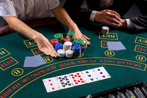 テーブルでポーカーをしているカップル。ブロンドの女の子とスーツを着た男。手を閉じます。オールインを賭ける