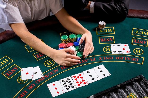 テーブルでポーカーをしているカップル。ブロンドの女の子とスーツを着た男。手を閉じます。勝ったチップを取る