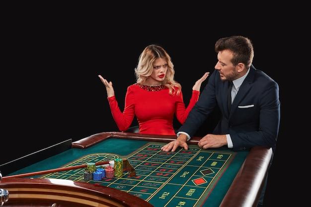 ルーレットをしているカップルがカジノで勝ちます。ギャンブル中毒。彼が失ったという事実のために女の子の不幸な男