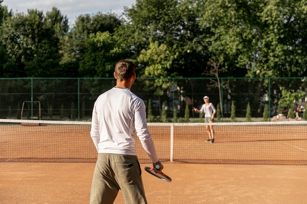 Couple playing tennis against each other