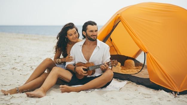 해변에 주황색 텐트와 ukelele를 재생하는 커플