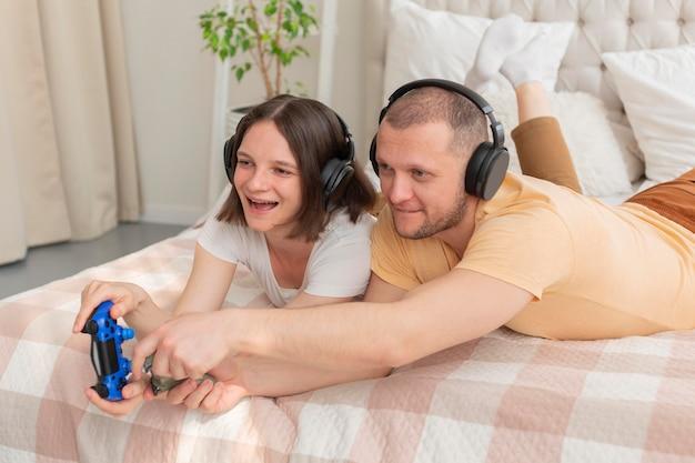 家で一緒にビデオゲームをしているカップル
