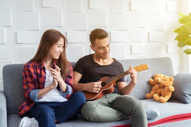 Couple playing ukulele at sofa. happy life in holiday.