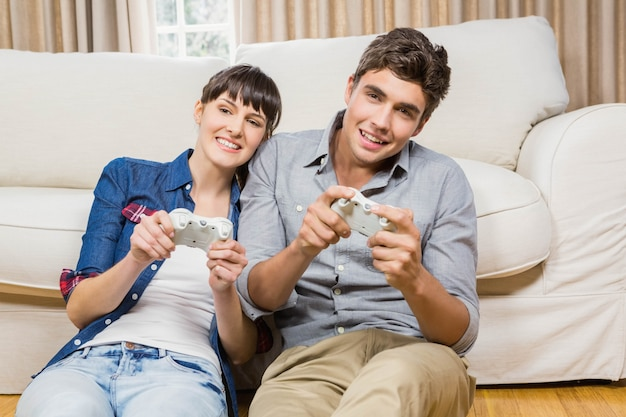 Couple playing video game in their living room