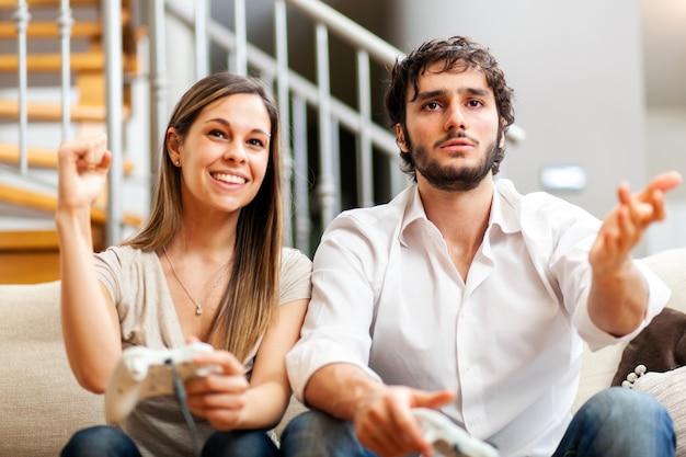 家でビデオゲームをしているカップル