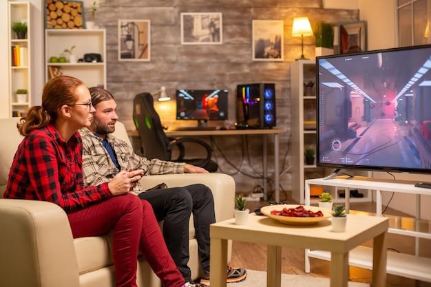 Coppia che gioca ai videogiochi sul grande schermo tv nel soggiorno a tarda notte.