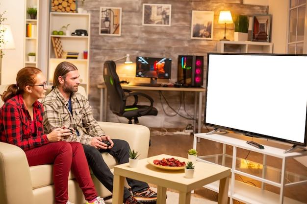 リビングルームで夜遅くに孤立した白いテレビ画面でビデオゲームをプレイするカップル