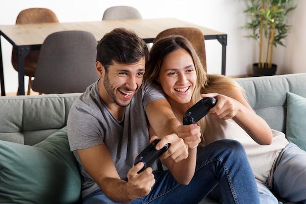 ビデオゲームのミディアムショットをしているカップル