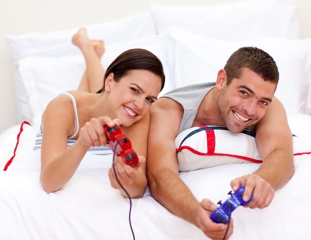 ベッドでビデオゲームをプレイするカップル