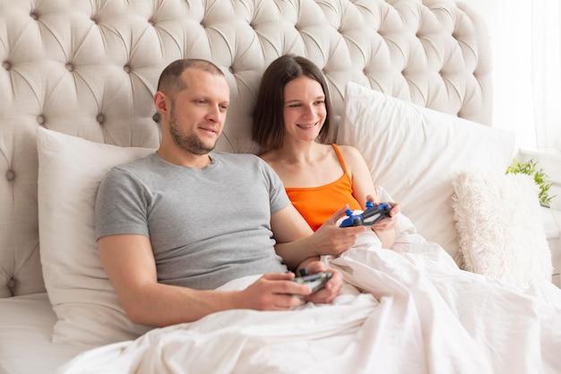 Пара играет в видеоигры в постели