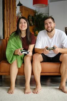 ソファでビデオゲームをしているカップル