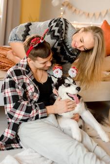 Пара играет с собакой в спальне