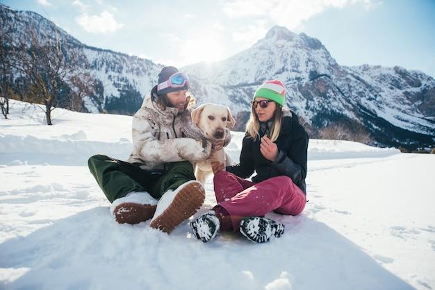 番目の雪に覆われた地面に山で犬と遊ぶカップル