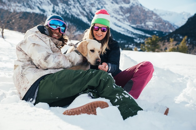雪に覆われた地面に山で犬と遊ぶカップル