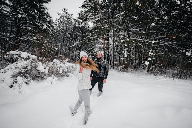 Couple playing with snow in the forest