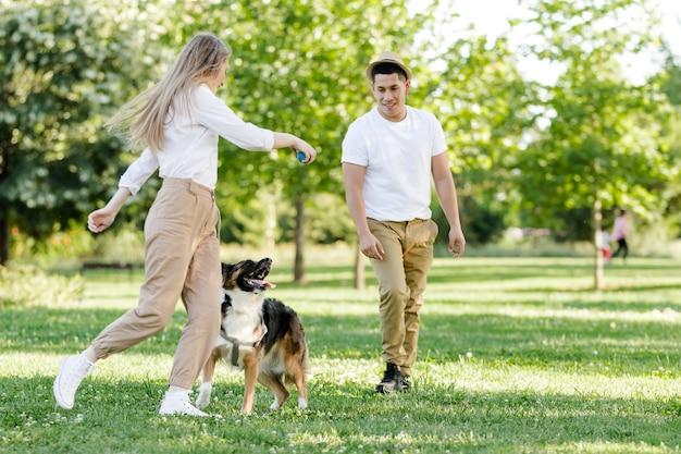 공원에서 자신의 강아지와 함께 재생하는 커플