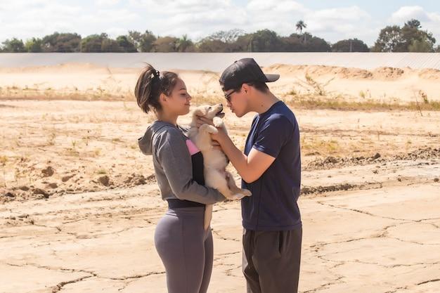 ビーチで子犬と遊ぶカップル。