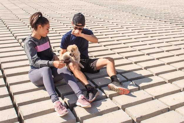 海岸で子犬と遊ぶカップル。