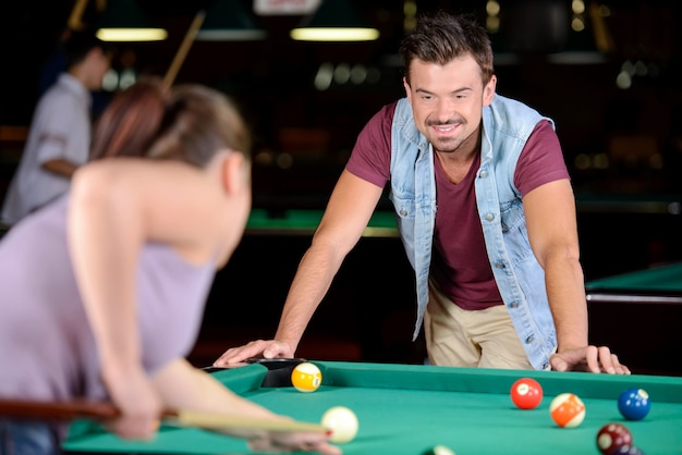 Couple plays billiards in the billiard club.