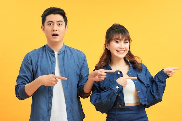Пара указывая пальцами в сторону, показывая место для копирования текста, стоящего на желтом фоне