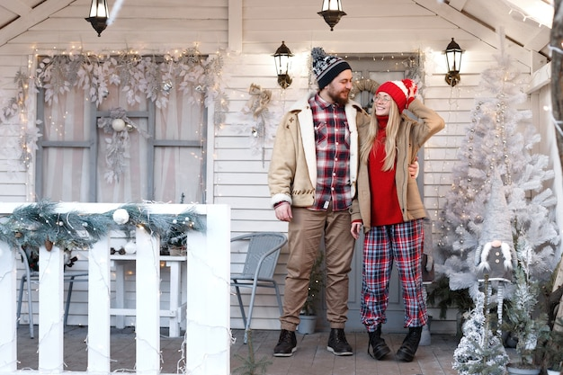 Couple on the porch of the white house on the winter holidays