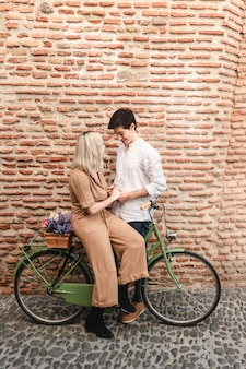 Couple posing against brick wall withbicycle