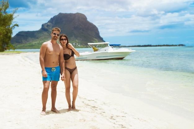 Пара позирует на пляже с яхтами и лодками