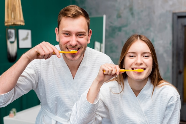 Couple posing in bathrobes while brushing their teeth