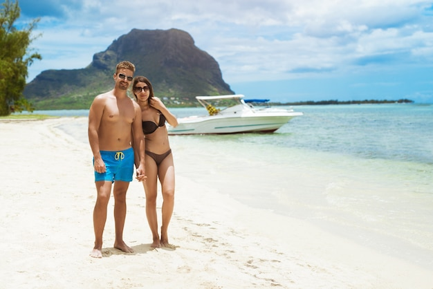 Couple posing at beach with yachts and boats
