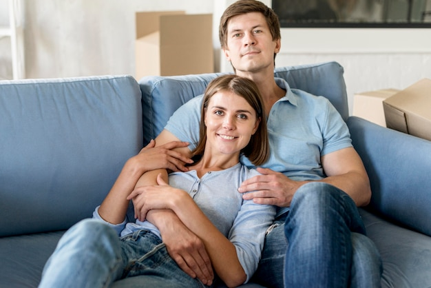 Couple posing on couch while packing to move house