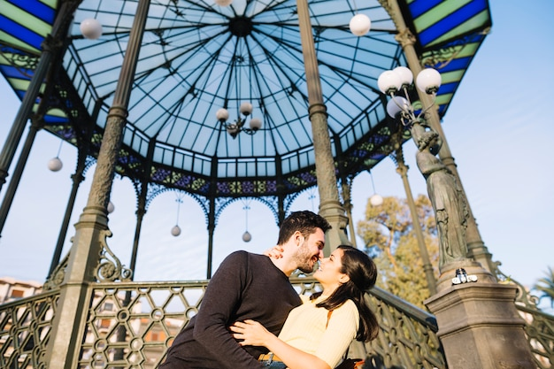 Couple posing in front of a pergola