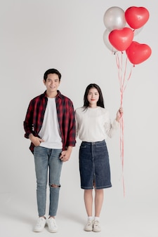 Couple posing on grey background with balloons heart.