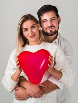 Couple posing and holding balloon and smiling