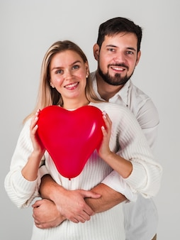 Couple posing and holding balloon