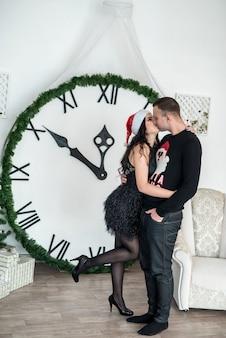 スタジオで真夜中を示す時計の近くでポーズをとるカップル
