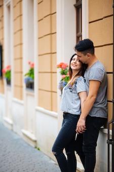 夏の天候でヨーロッパの都市の路上でポーズのカップル