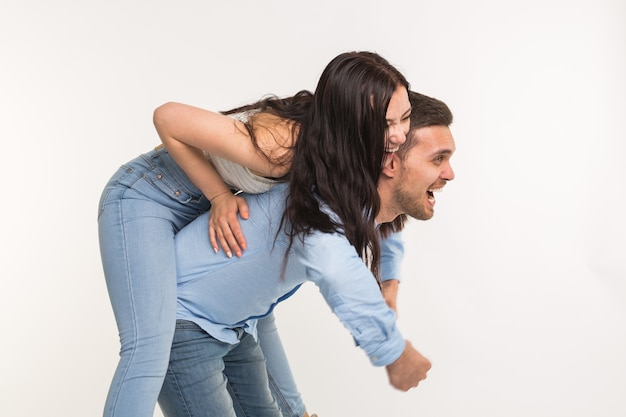 Пара позирует на белом фоне - смешной мужчина держит женщину на спине