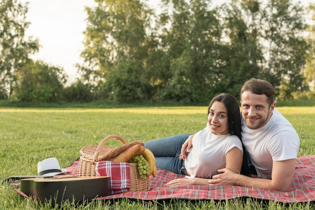 Couple posing on a picnic blanket