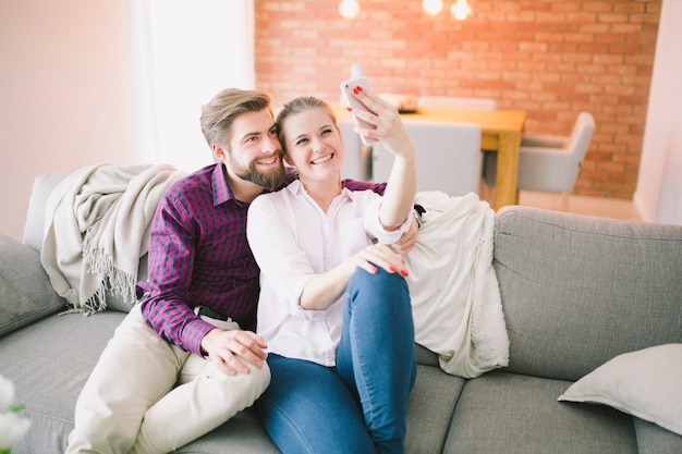 Couple posing for selfie on couch