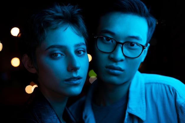 青いネオンの光の中で夜に一緒にポーズをとるカップル