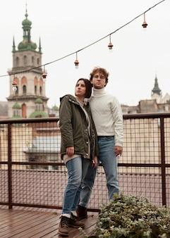 屋根の上で一緒にポーズをとるカップル
