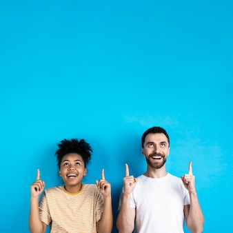 Couple posing while pointing up