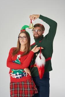 ベルとクリスマスの靴下でポーズをとるカップル