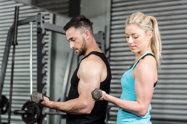 Couple posing with dumbbells at crossfit gym